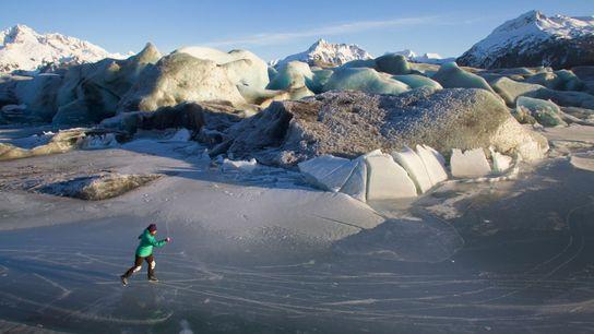 Une femme fait du patin à glace devant le glacier Sheridan, en périphérie de la ville ...