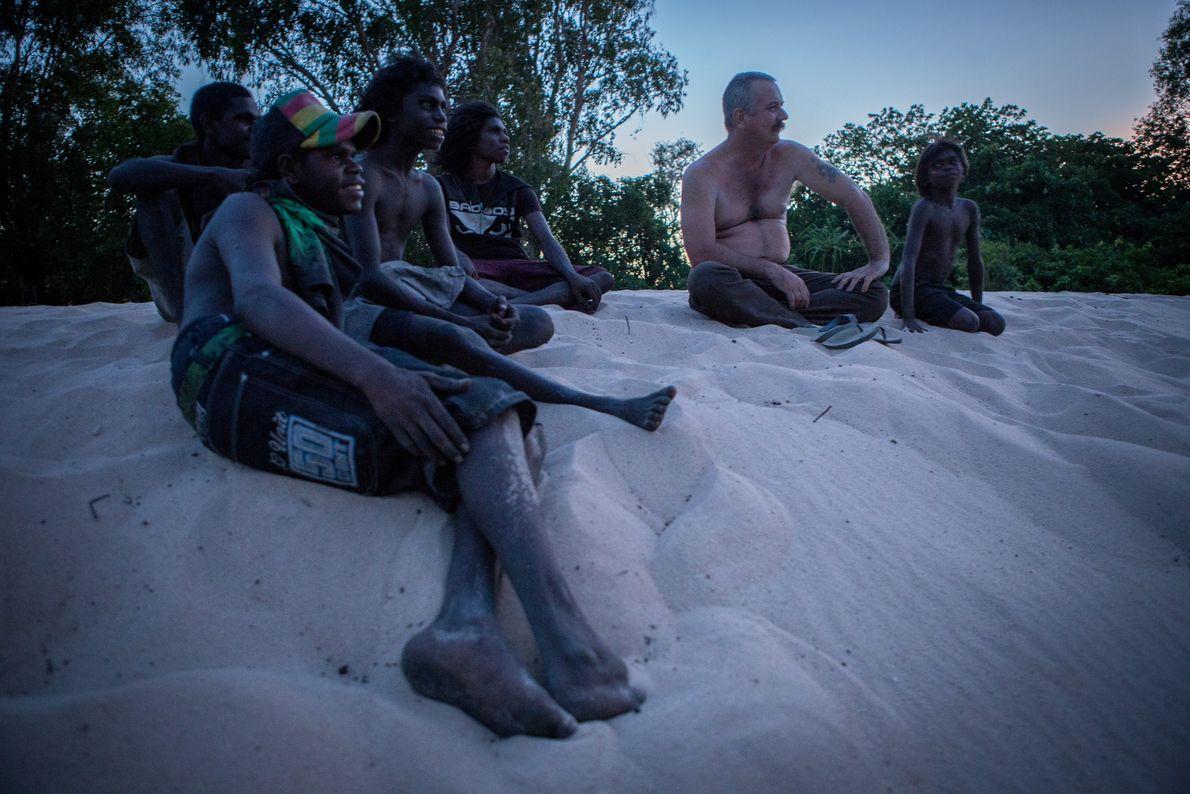 Assis en compagnie d'une famille aborigène sur une plage de sable à proximité d'un billabong, Roger ...