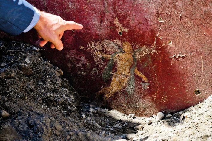 Le directeur du Grand Projet Pompéi montre du doigt un cupidon ornant une maison à proximité ...