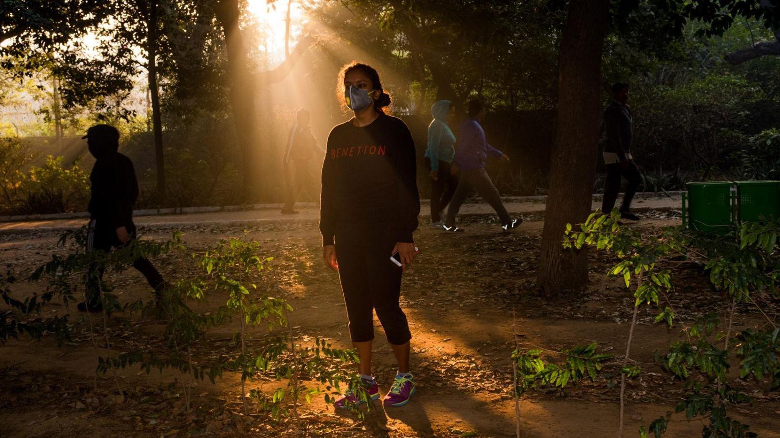 Une jeune femme porte un masque pendant sa promenade matinale à Lodi Gardens.