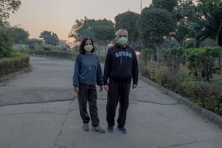 Un couple porte un masque lors de leur promenade matinale à Astha Kunj Park, près du ...