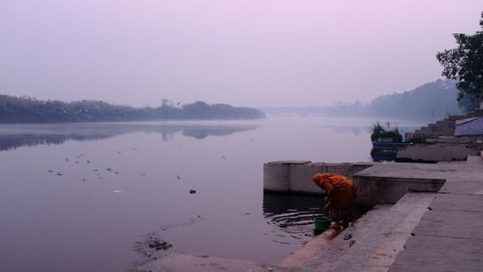 Une femme va chercher de l'eau au petit matin, dans la rivière Yamuna.