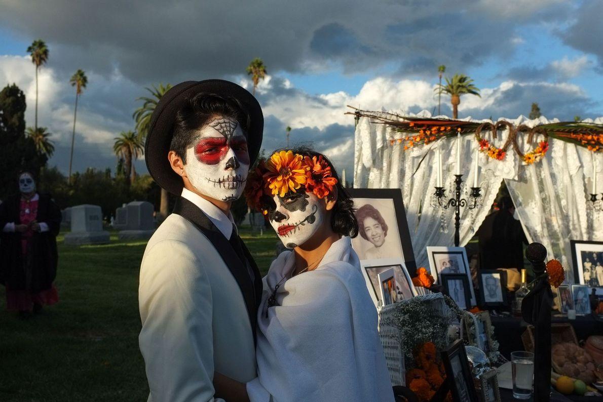 Un couple représentant Catrina et Catrín prennent la pose devant une ofrenda, ces autels érigés en ...