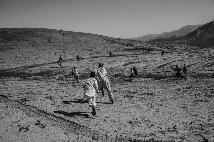 De jeunes Afghans ramassent des munitions utilisées après un entraînement de tir par les forces belges ...