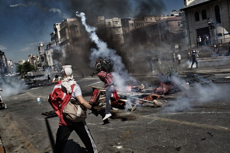 Un manifestant jette une capsule de gaz lacrymogène sur des policiers, à Istanbul, Turquie, le 1er ...