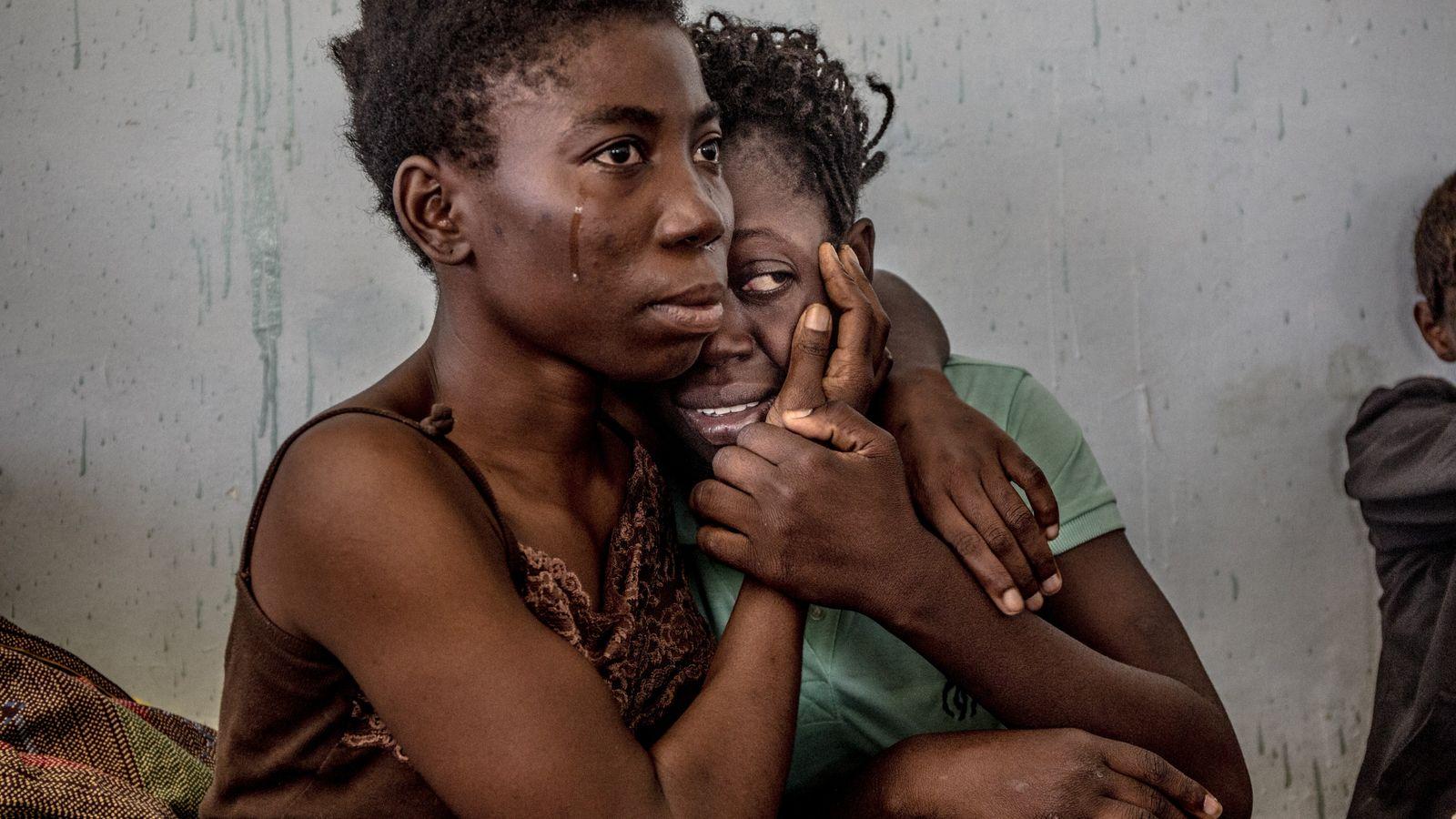 Des migrantes nigériennes s'embrassent en pleurant dans un centre de détention pour réfugiés à Surman, en ...