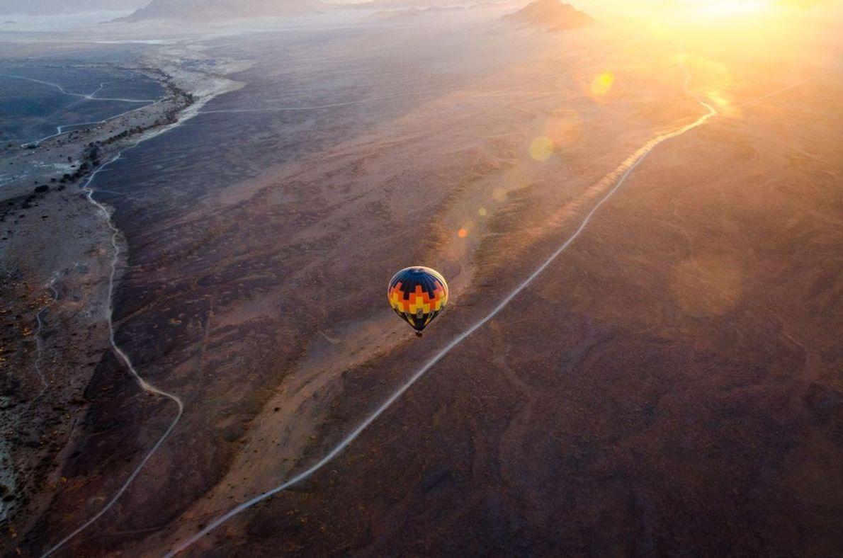 « Un vol en montgolfière au coucher du soleil, au-dessus des dunes de Sossusvlei, en Namibie, ...