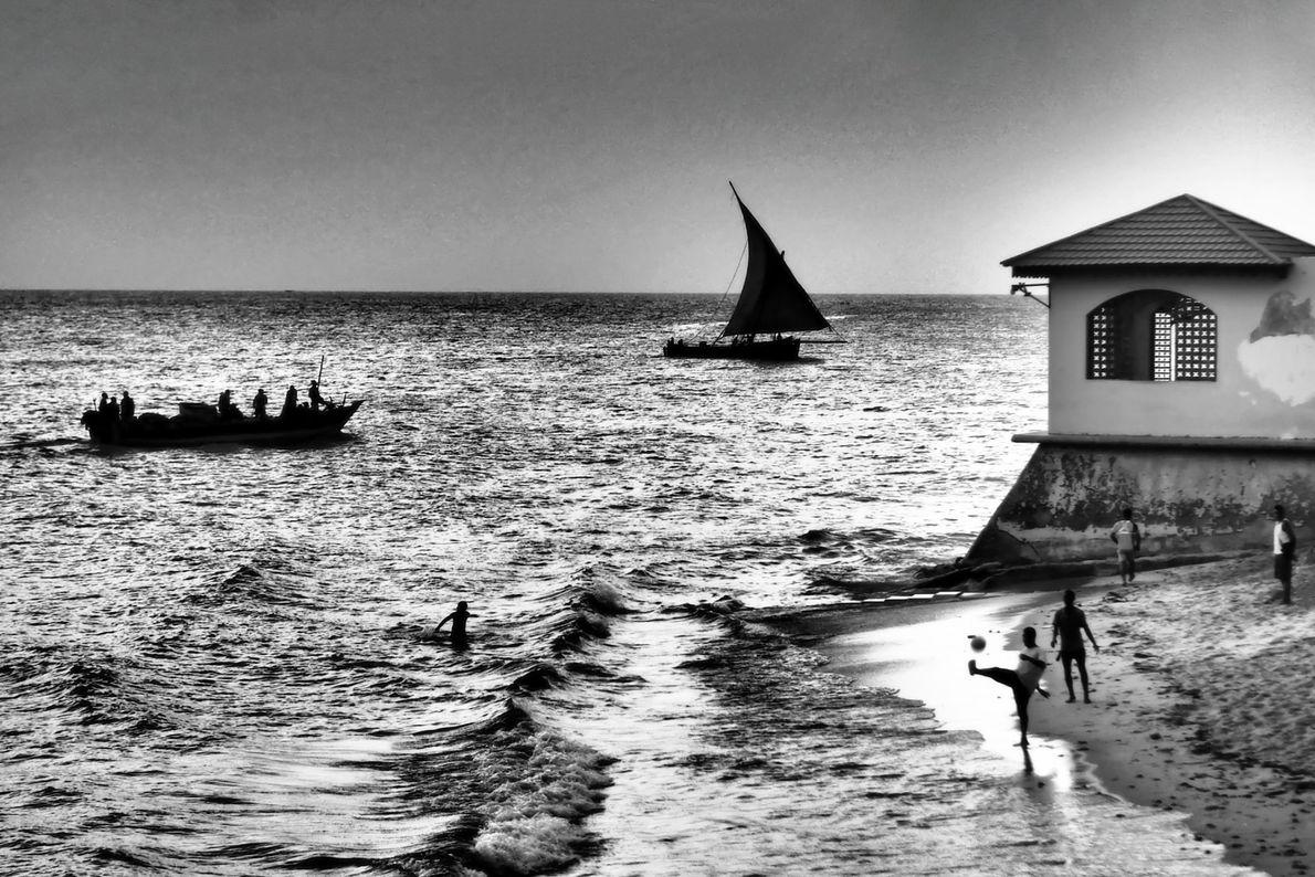 Plaisanciers, marins, nageurs et joueurs de football profitent à leur façon d'une plage ensoleillée en bordure ...