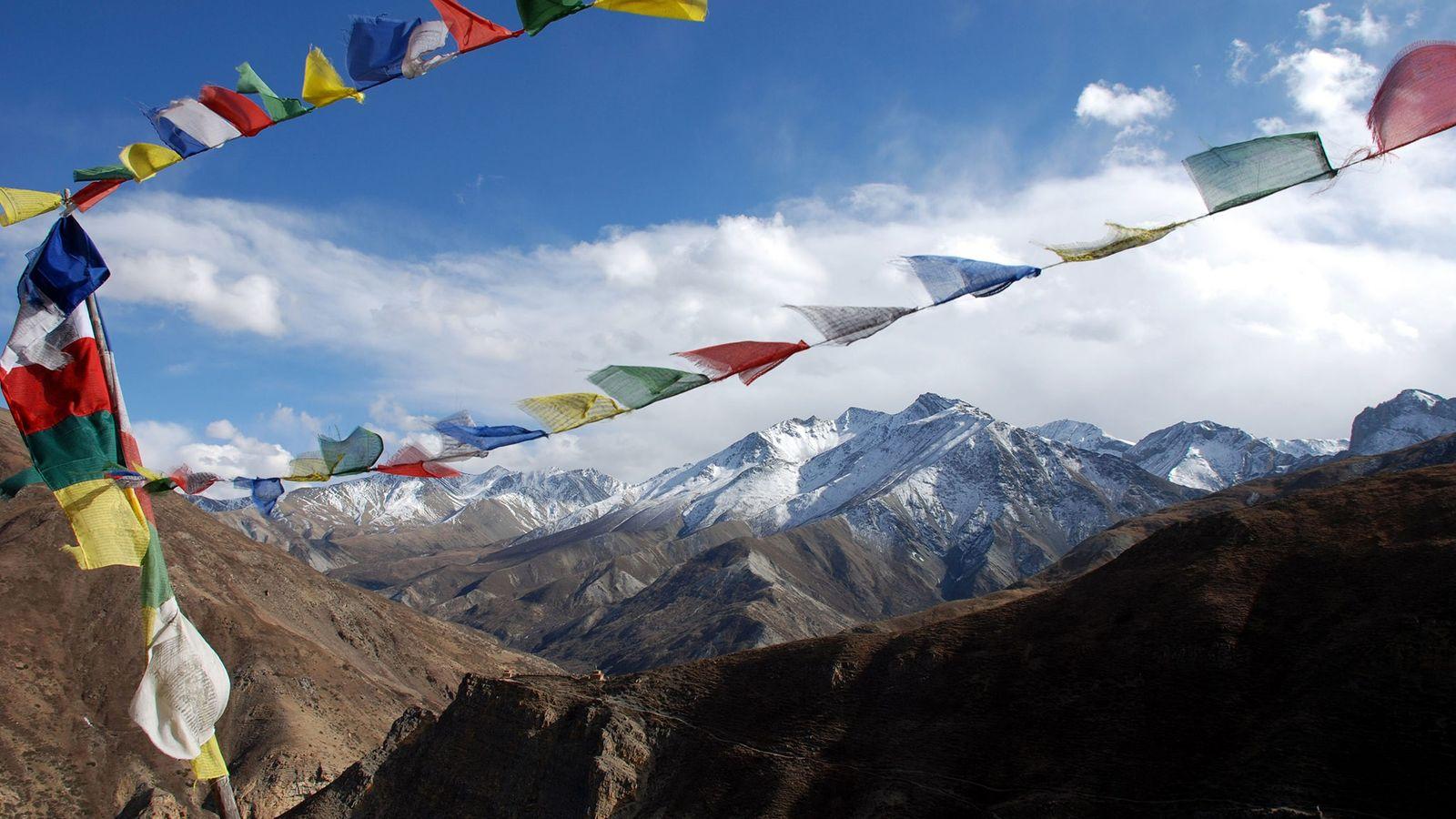 Des drapeaux de prières bouddhistes flottent au vent au sommet d'un col haut dans l'Ouest du ...