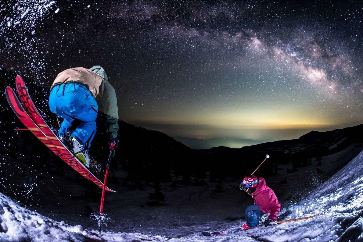 Des aventuriers skient éclairés par la lumière de la lune.