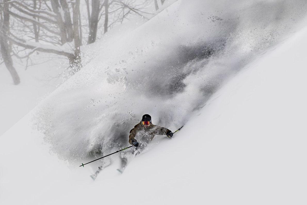 Un skieur fend la neige dans un mouvement rapide.