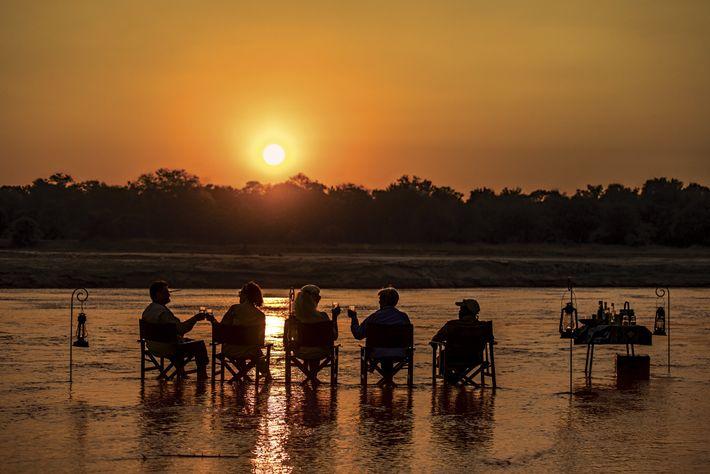 Après une journée de marche à travers le parc national de Luangwa Sud, les résidents se ...