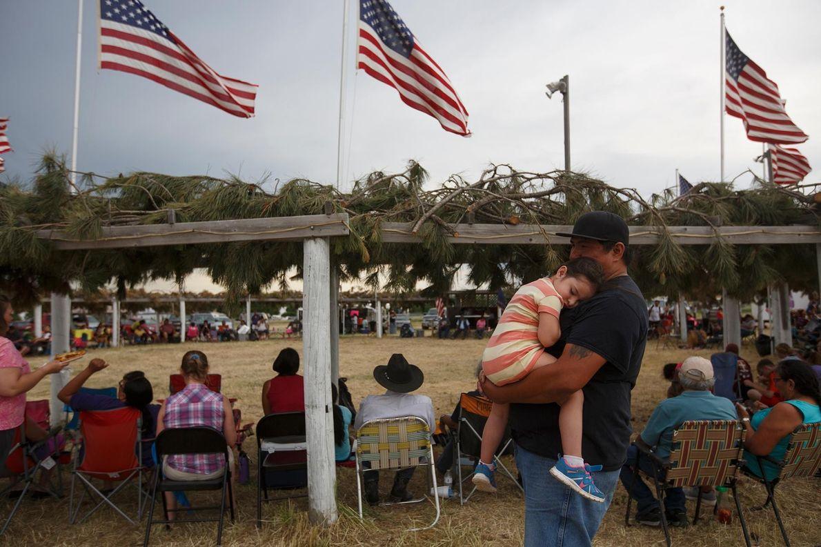 Lors d'un entracte au rassemblement de Batesland, Kevin Whiteface porte sa fille endormie, Liv.
