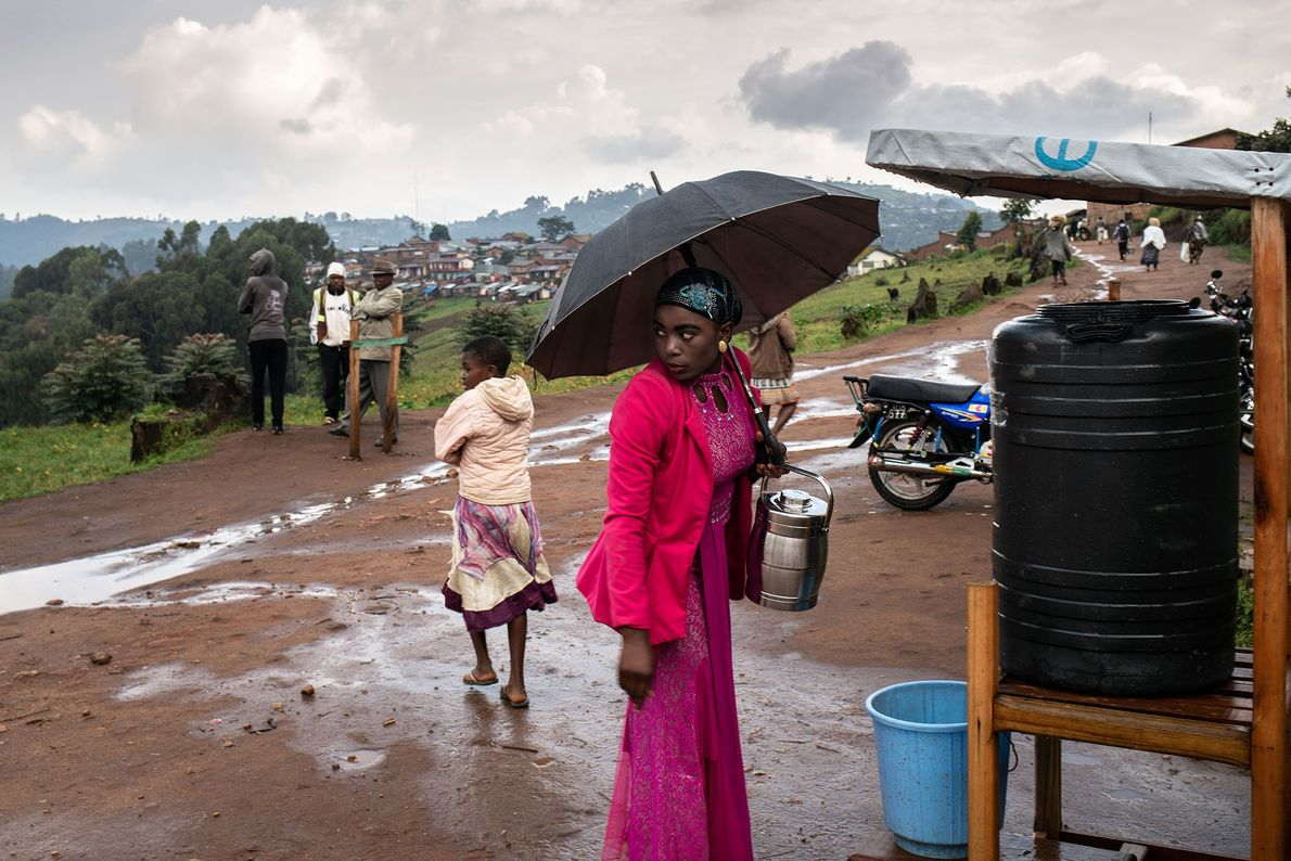 Une femme s'arrête pour laver ses mains avec une solution à base de chlore, après s'être ...