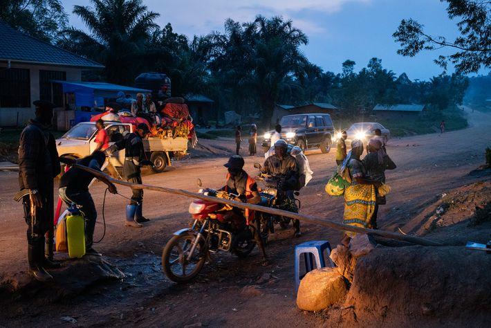 Des travailleurs lavent les roues des véhicules à l'eau chlorée et vérifient les températures corporelles des ...