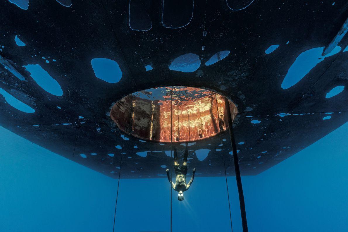 Cédric Gentil, membre de l'équipe de soutien, flotte tête en bas sous la barge, à côté ...