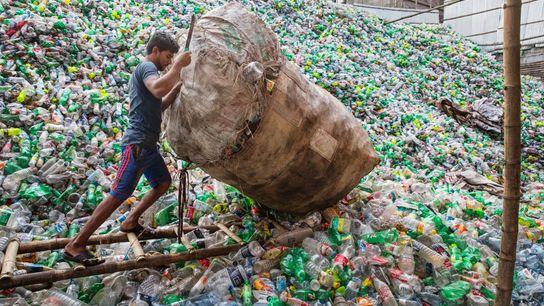 À Dhaka, au Bangladesh, un homme déverse des bouteilles en plastique sur un monticule d'ordure.