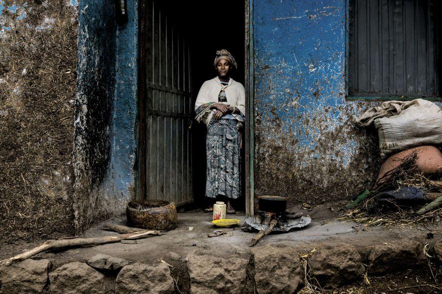Une femme prépare le déjeuner sur le porche de sa maison des plateaux d'Éthiopie, où le ...