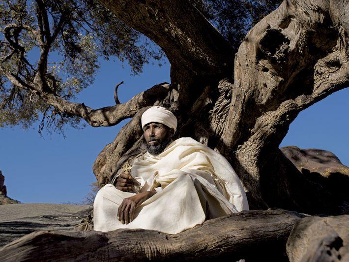 Le prêtre résidant de l'église Abuna Yemata Guh s'accorde une pause sous un olivier sacré avant ...