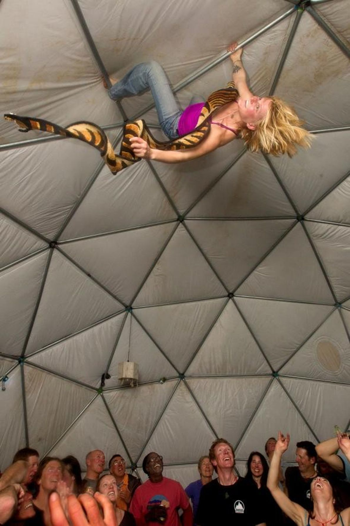 Une alpiniste démontre ses talents de grimpeuse sur la structure d'une tente lors d'une soirée au ...