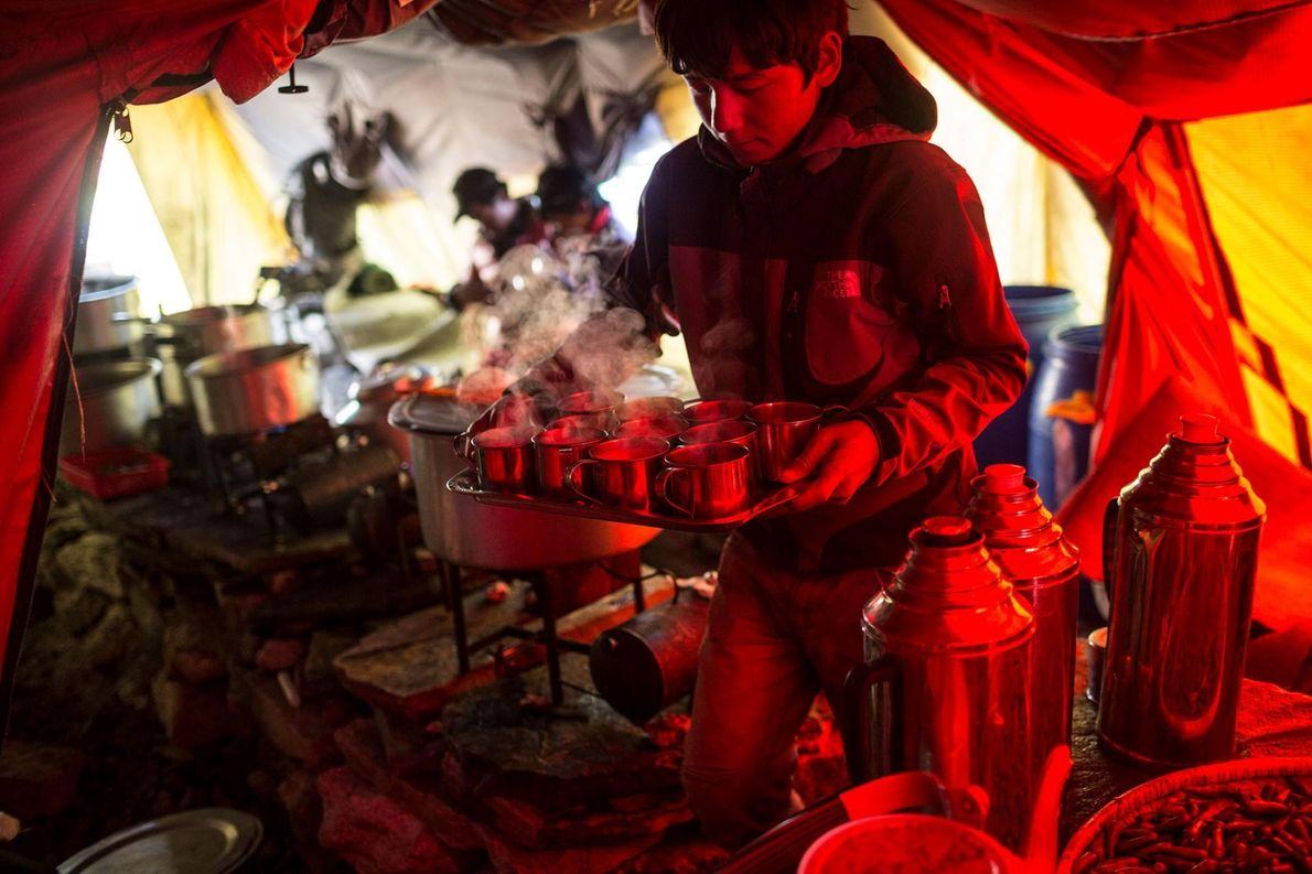 Un homme porte un plateau rempli de boissons chaudes dans la cuisine du camp de base ...