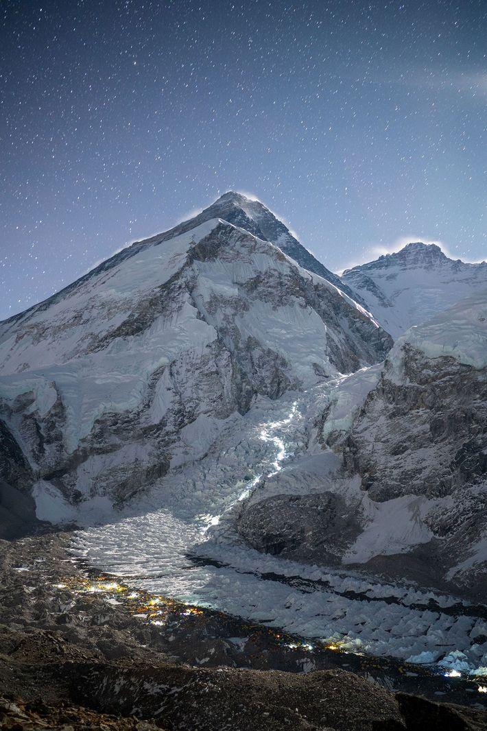 Des lampes frontales illuminent le chemin qu'empruntent les alpinistes du camp de base à la cascade ...