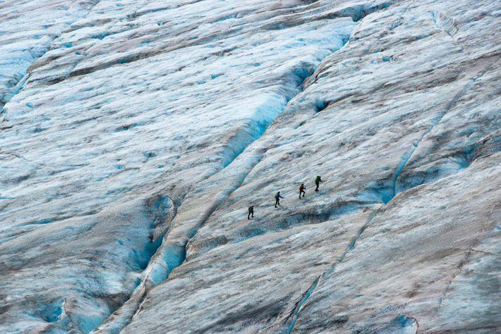 Des alpinistes sur glace se suivent en formant une ligne parallèle à une fissure sur le ...