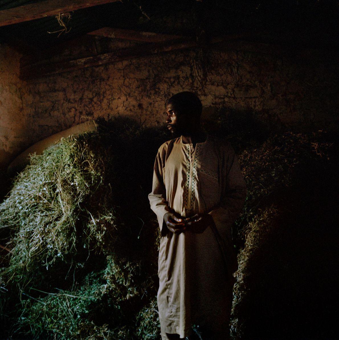 Timothy, un fermier nigérian, se tient près d'un stock de piments séchés.