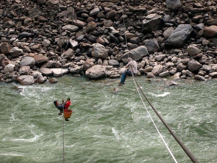 Suspendu à une tyrolienne, Fritz Hoffmann (à droite) photographie les locaux qui traversent le fleuve Nu ...