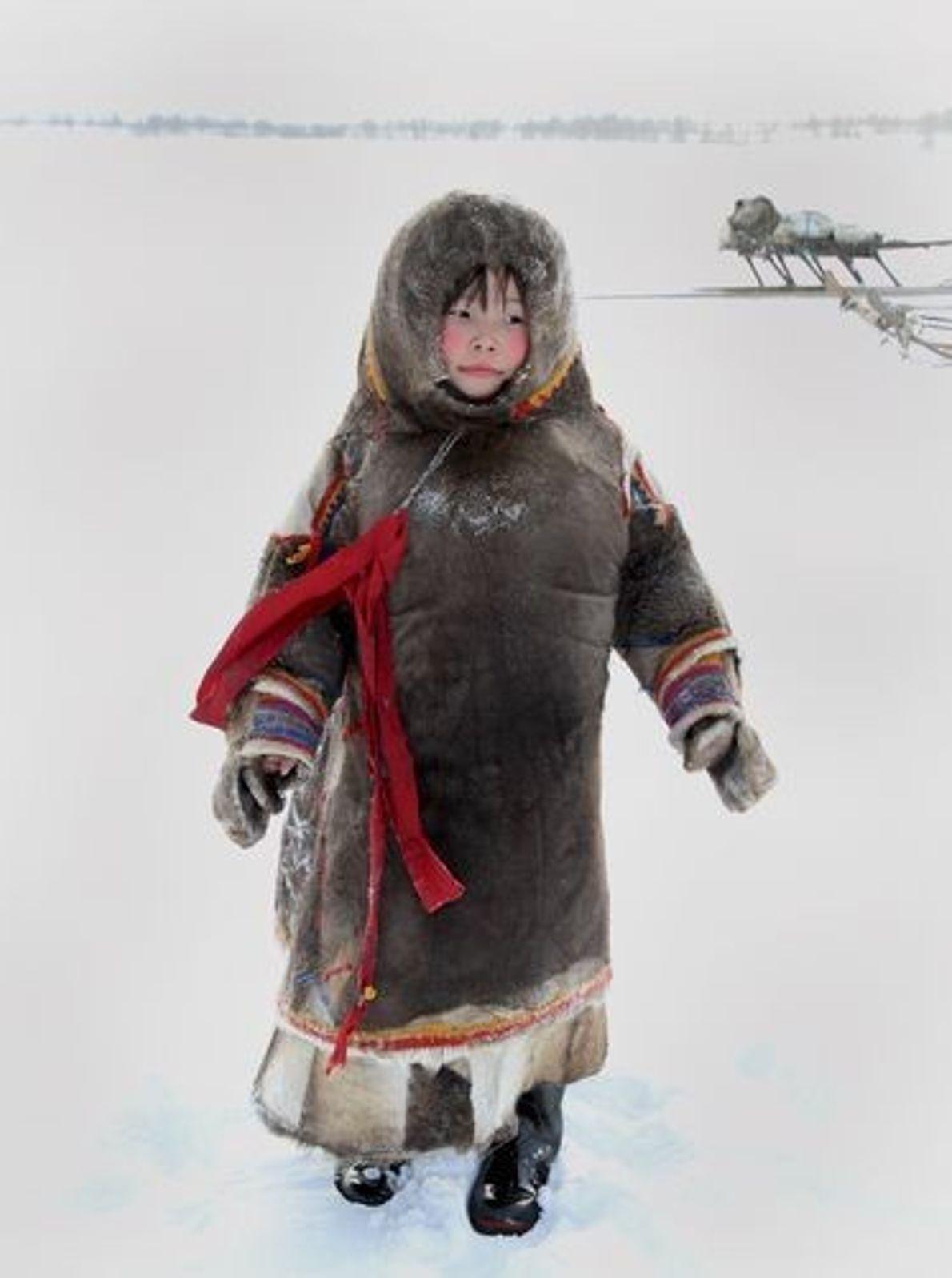 Une fillette nénette de la péninsule de Yamal en Sibérie se protège du froid avec ses ...