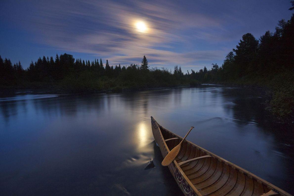 Un clair de lune illumine un canoë fait en écorce de bouleau sur la rivière Allagash, ...