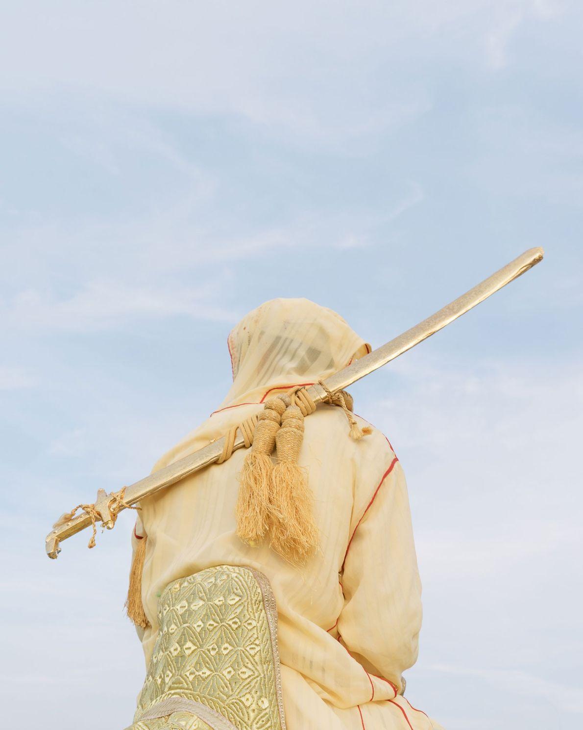 Ce cavalier est vêtu d'une djellaba, un vêtement ample doté de manches longues et d'une capuche, ...