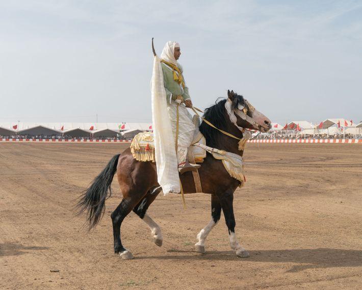 Un cavalier se tient debout au-dessus de sa selle pour ravir la foule, avant de rejoindre ...
