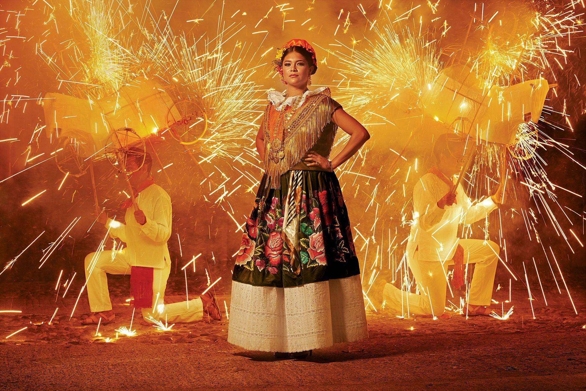 Cette femme porte une robe traditionnelle de Tehuantepec, au Mexique. Les fleurs sont brodées de fil de soie sur du tissu de velours et la robe est ornée de bijoux en or qui ont été transmis de génération en génération. Les deux hommes que l'on aperçoit en arrière-plan sont appelés toritos, « petits taureaux » en français.