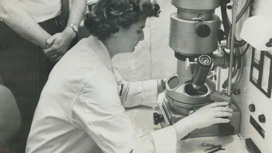 La scientifique June Almeida devant un microscope électronique en 1963, à l'Institut ontarien de recherche sur ...