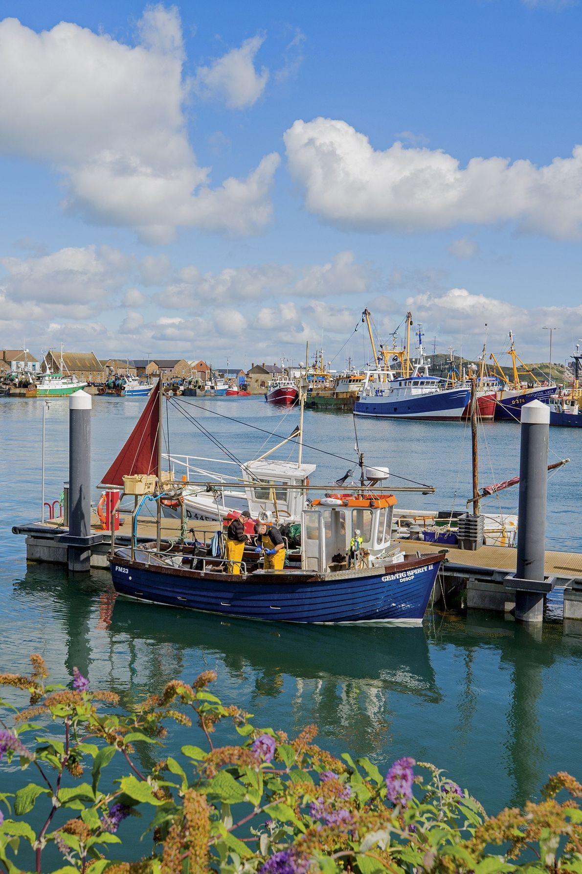 Deux hommes travaillent durement sur un bateau de pêche dans le village de Howth, la péninsule ...