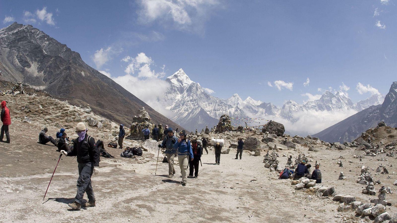 Des Sherpas et des randonneurs traversent le col de Thokla, au Népal, en direction du mont ...