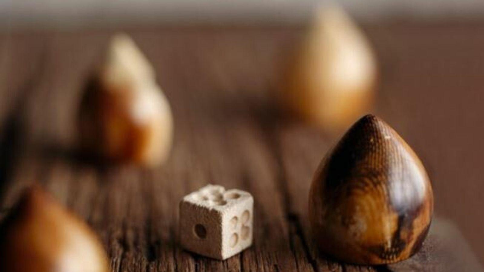 Un dé en os et des glands en ivoire mesurant 2,5 centimètres de haut, sans doute des ...