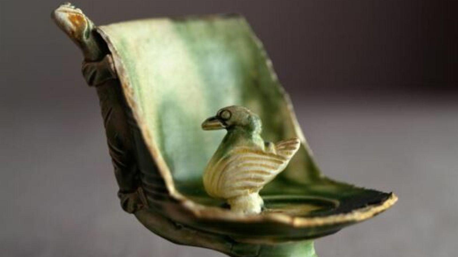 Un petit canard garde l'ouverture interne d'une paille façonnée dans une coupe de presque 9 centimètres de ...