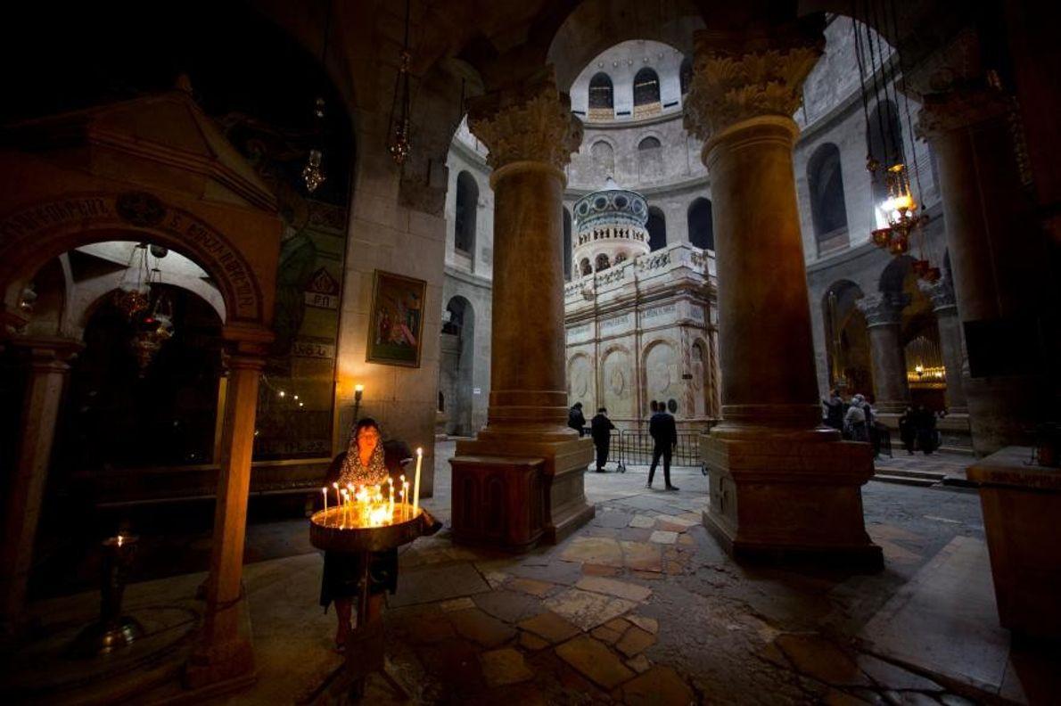 Des fidèles allument des cierges dans l'église du Saint-Sépulcre qui, selon la tradition, abriterait le lieu ...