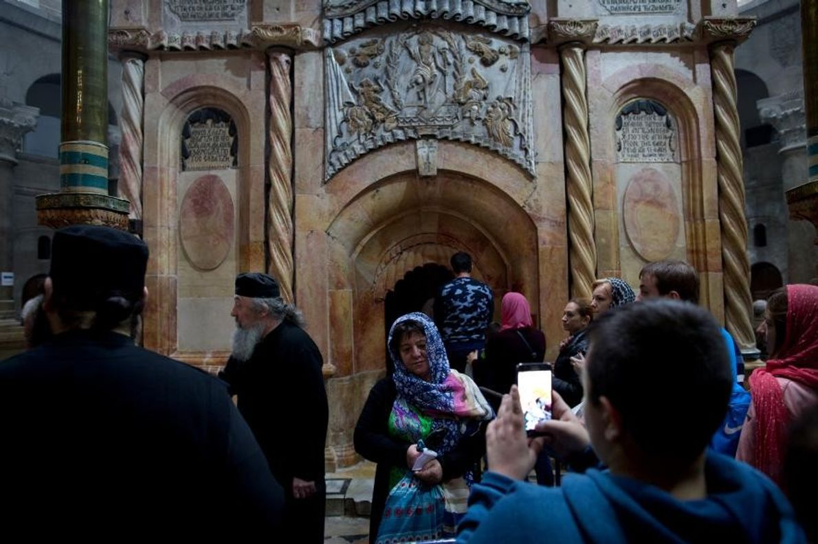 Une femme pose devant l'édicule qui abrite le tombeau de Jésus.