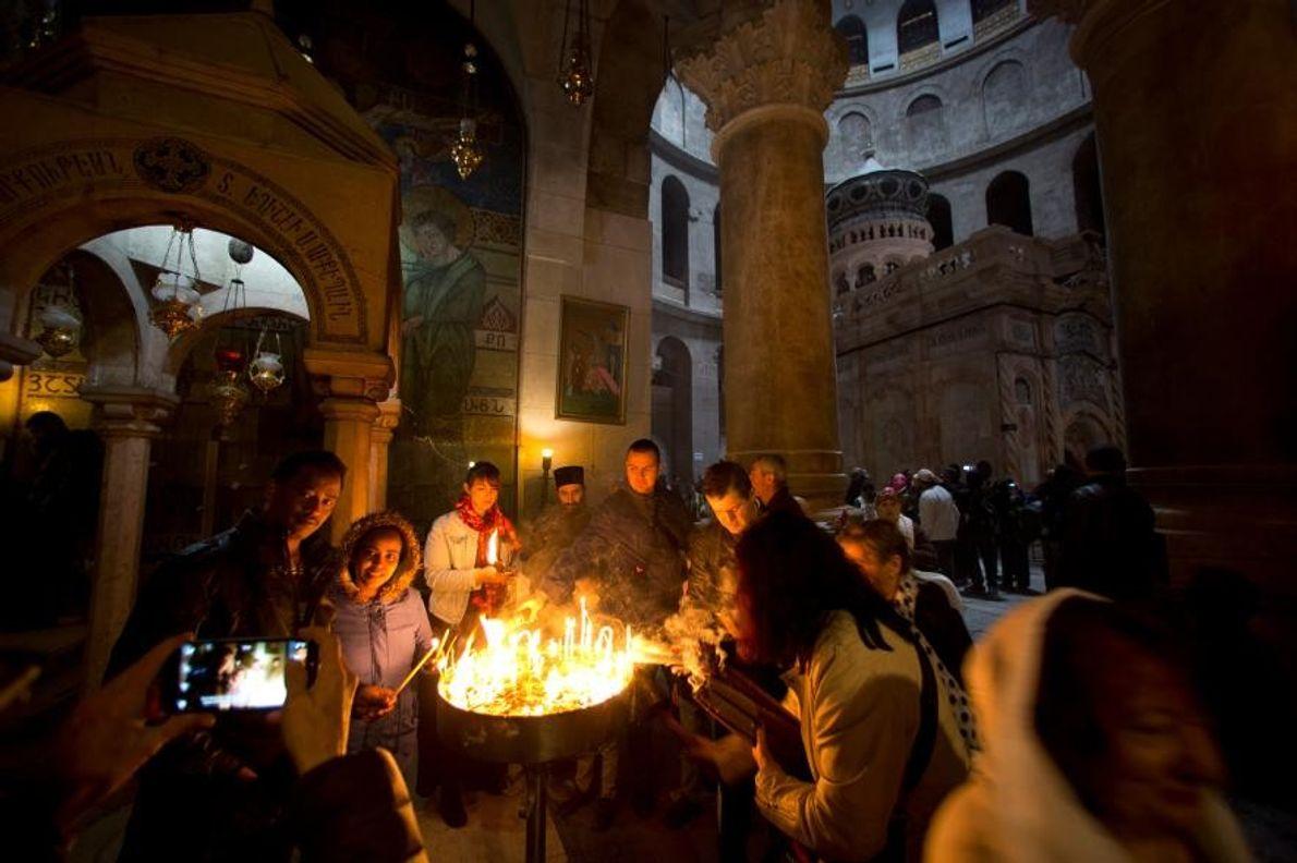 Des visiteurs allument des cierges à l'entrée de la rotonde, au sein de l'église du Saint-Sépulcre.