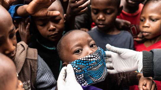 Un jeune garçon s'essaye au port du masque pendant une distribution de nourriture aux familles vulnérables ...