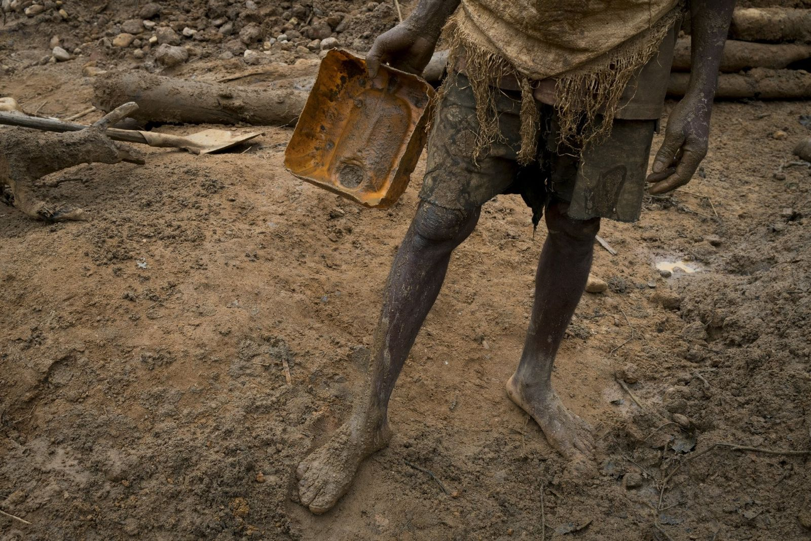 Un homme couvert de boue tient un morceau de jerrycan en plastique qu'il utilise pour ôter ...