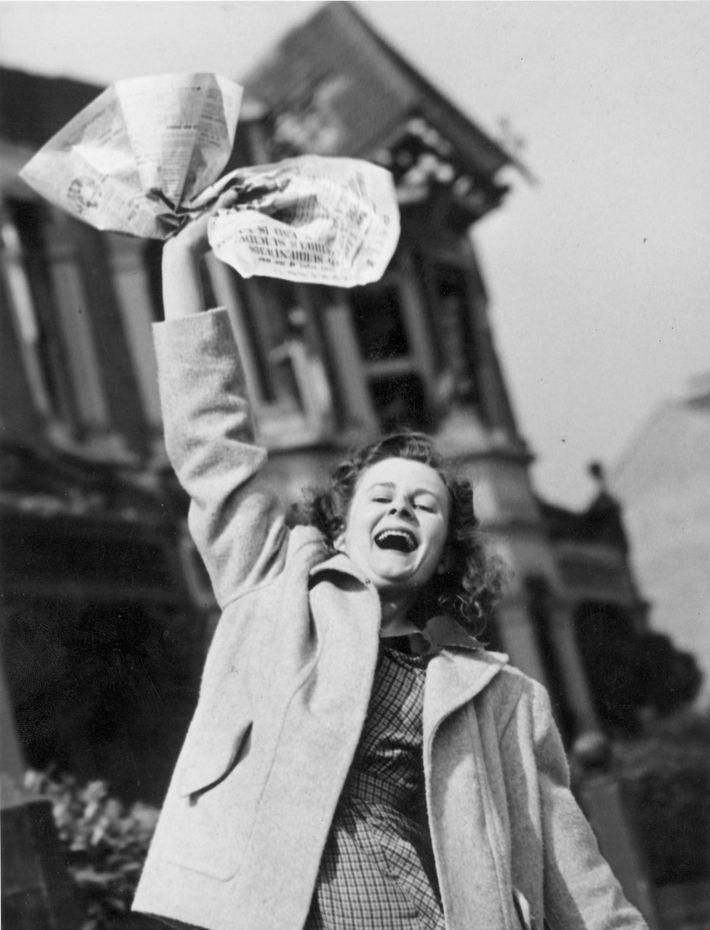 Pat Burgess agite un journal qui annonce la victoire des Alliés. Elle espère que son mari, ...