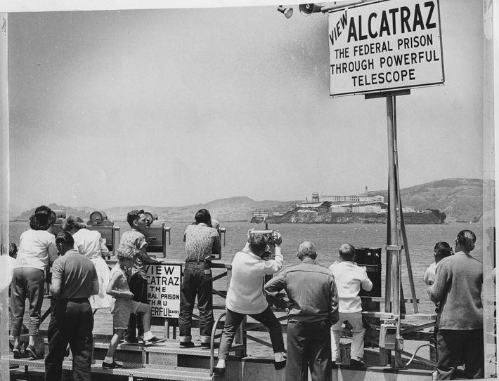 Sur cette photo de 1962, les badauds observent Alcatraz à travers des jumelles après une tentative ...