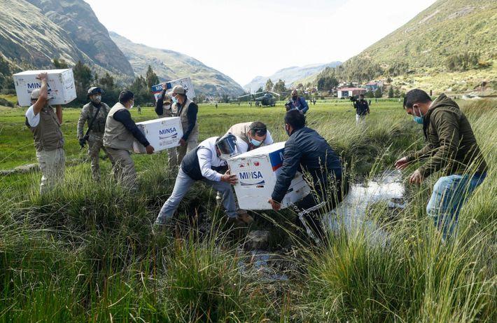 Des membres de l'armée péruvienne transportent avec précaution des boîtes remplies de vaccins Oxford-AstraZeneca dans une ...