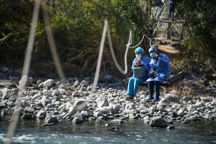 Le 2 juillet 2021 au Pérou, des soignants traversent en tyrolienne la portion du fleuve Colca qui passe ...
