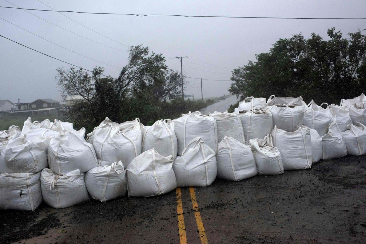 La pluie d'abat sur une barrière de sacs de sable placée à Montegut avant l'arrivée d'Ida ...