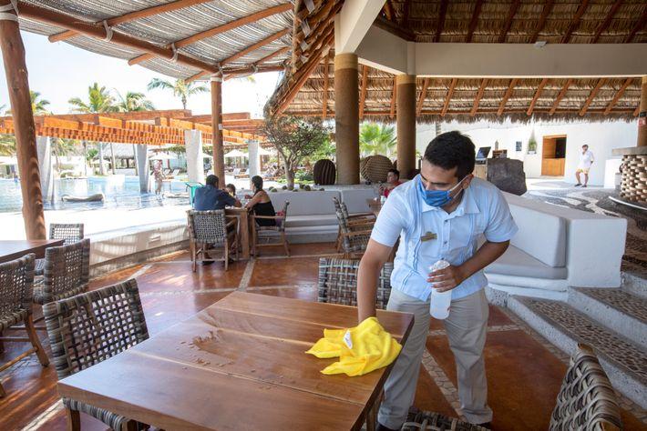 Le serveur d'un restaurant de La Paz, au Mexique, désinfecte une table. Le secteur du tourisme pèse ...